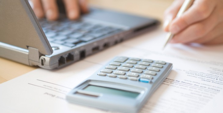 Woman's Hands Calculating Home Finances At Desk
