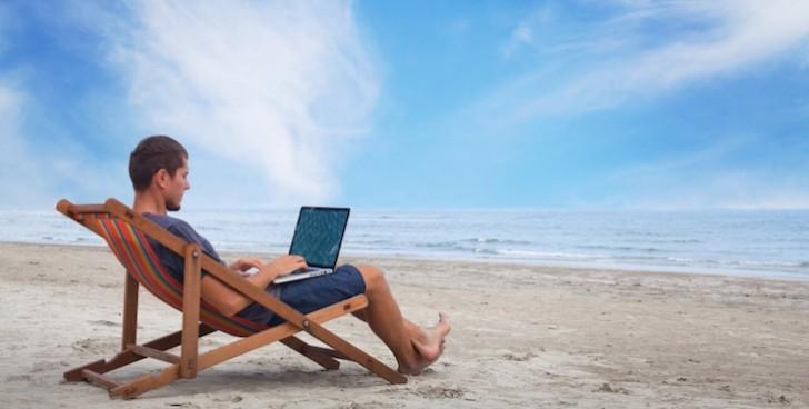 海でパソコン作業する人