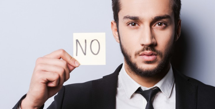 I said No. Handsome young man in formalwear holding adhesive note while standing against grey background
