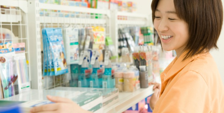 Salesclerk of convenience store tidying up goods