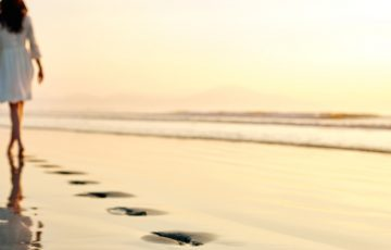 Footprints on shore with woman walking in distance at sunset