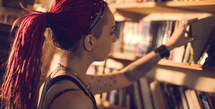 Woman with dreadlocks choosing a book from bookshelf.