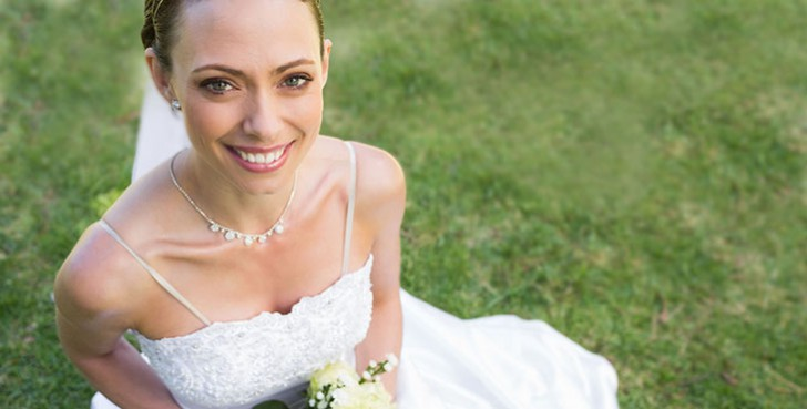 High angle portrait of young bride holding flower bouquet while sitting in garden