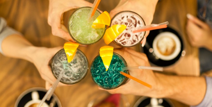 Friends toasting with colorful drinks in a cafe