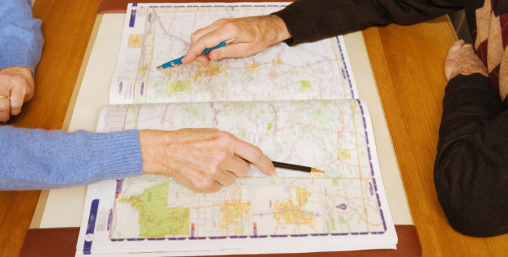 Senior couple pointing at destinations on map