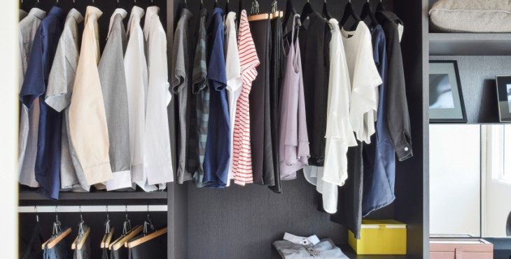 modern closet with row of cloths hanging in black wardrobe