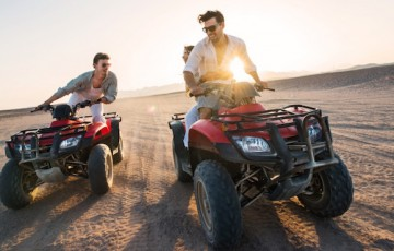 Playful people on quad bikes in the desert.