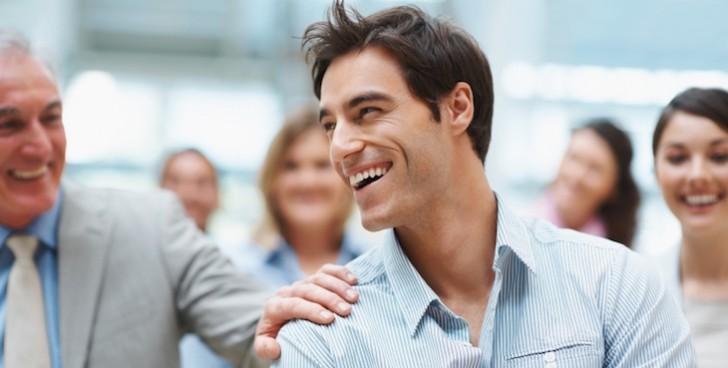 Smart young business executive enjoying success with team mates