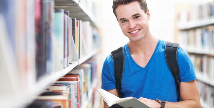 Shot of a handsome young man smiling as he holds a library book