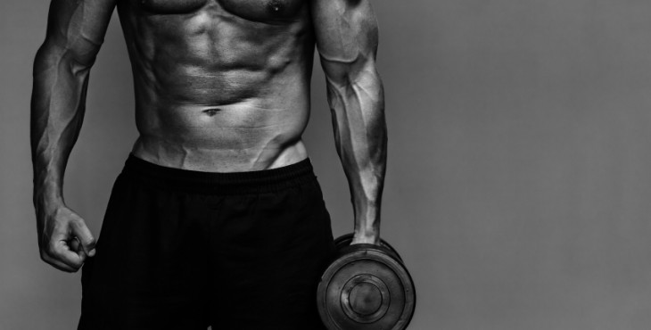 Close up of muscular bodybuilder guy doing exercises with weights over grey background. Black and white