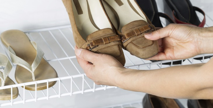 Horizontal image of females taking out a pair of brown shoes from the wall mount rack to wear