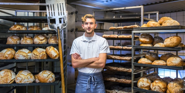 Baker in his bakery baking bread baker posing in his bakery bakehouse in the early morning between fresh baked artisan bread
