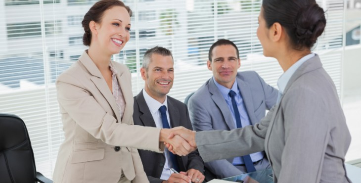Young pretty applicant shaking hands with future employers in bright office