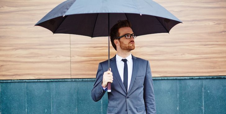 Young entrepreneur with briefcase standing outside under umbrella