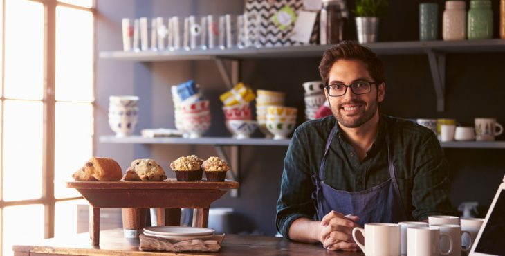 Portrait Of Male Coffee Shop Owner Standing Behind Counter