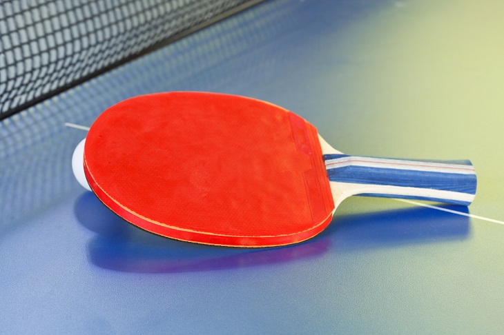 red bat, tennis ball on blue ping pong table close up