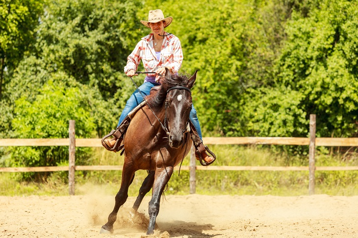 Active western cowgirl woman in hat training riding horse. American girl in countryside ranch. Horseback sport activity.