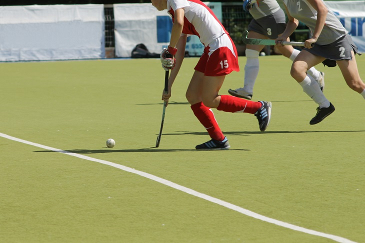 Women field hockey players with ball on the grass. Young professional teams in competition