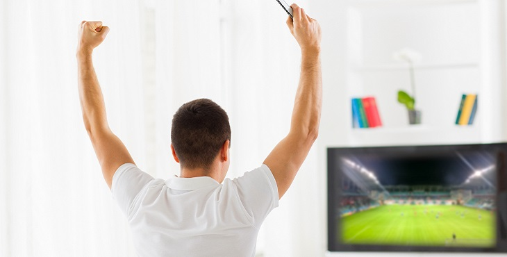 happy man watching football on tv at home