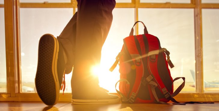 Traveler stands near the backpack at airport.